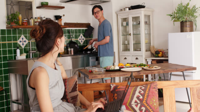 wide shot of a young woman using a laptop and talking to her boyfriend whilst he is cooking in the background - married stock videos & royalty-free footage