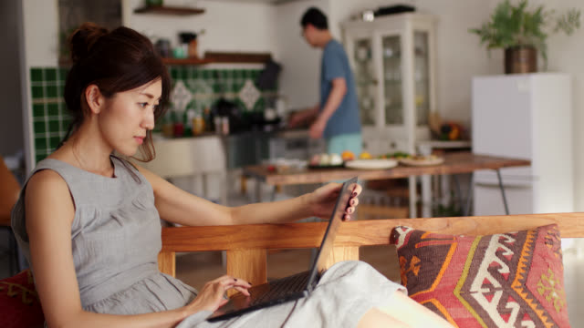 wide shot of a young woman using a laptop and talking to her boyfriend whilst he is cooking in the background - teleworking stock videos & royalty-free footage