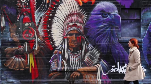 vídeos de stock, filmes e b-roll de wide shot of a young woman walking past street art depicting an indian chief in stokes croft bristol uk no - bristol inglaterra