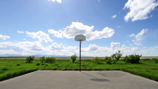 wide shot of abandoned basketball court on lush green grass prairie under a puffy white cloud filled blue sky. - wide stock videos and b-roll footage