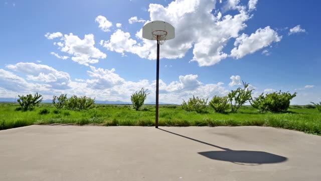 vidéos et rushes de wide shot of abandoned basketball court on lush green grass prairie under a puffy white cloud filled blue sky. - panier de basket