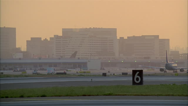 wide shot of activity at lax at twilight / low angle view of american airlines jet taking off over camera / los angeles - number 6 stock videos & royalty-free footage