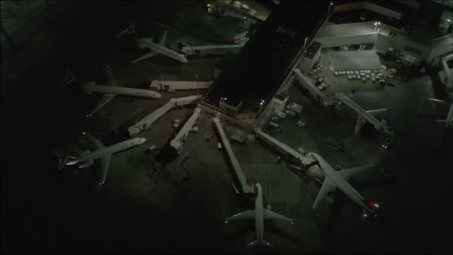 Wide shot of airplanes at the gates with attached jet bridges at the LaGuardia Airport at night