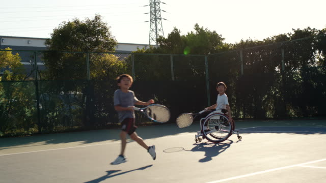 slo mo wide shot of an adaptive tennis player playing doubles - physical disability stock videos & royalty-free footage