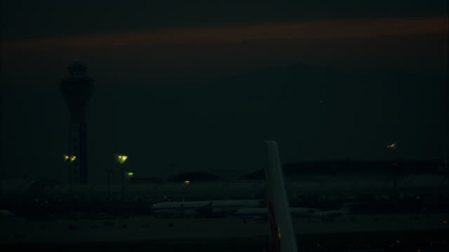 wide shot of an aircraft landing at the beijing airport at night. - luftfahrtindustrie stock-videos und b-roll-filmmaterial