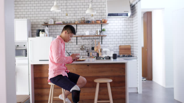 wide shot of an amputee male sitting in the kitchen using his smartphone - pianale da cucina video stock e b–roll