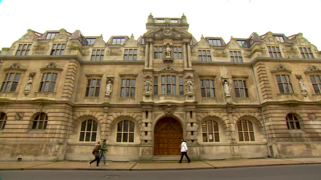 wide shot of an entrance via a large wooden door dominated by statues, to oriel college, oxford - 20 24 years stock videos & royalty-free footage