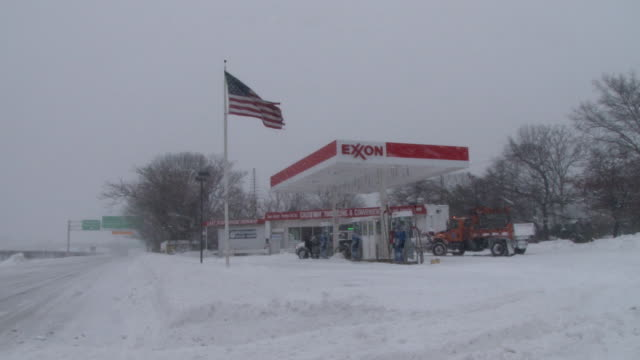 wide shot of an exxon gas station and flag blowing during the height of a blizzard on long island - exxon stock videos & royalty-free footage