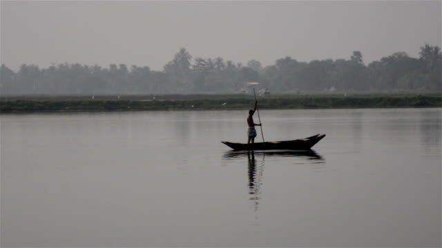 Wide shot of an Indian lone boatman rowing over a desolate lake.