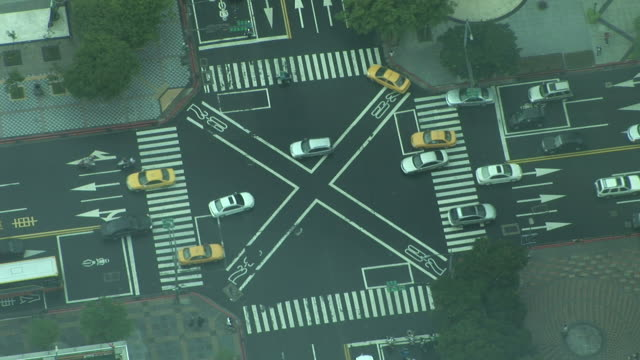 wide shot of an intersection in taipei taiwan - zebramuster stock-videos und b-roll-filmmaterial