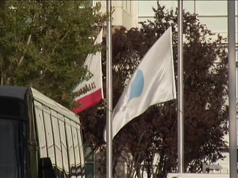 wide shot of apple headquarters with sign in foreground and building in background shot zooms in on flags in front of entrance flying at half staff... - walt disney animation studios stock videos & royalty-free footage