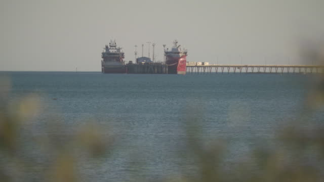 wide shot of aqua blue water of roebuck bay pan to broome jetty at port authority minyirr broome / wide shots of cargo ships at the end of jetty /... - outcrop stock videos & royalty-free footage