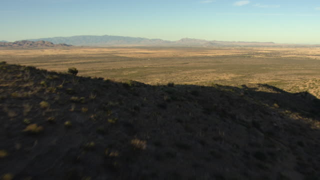 wide shot of arid plains behind a hill in arizona - shrubland stock videos & royalty-free footage