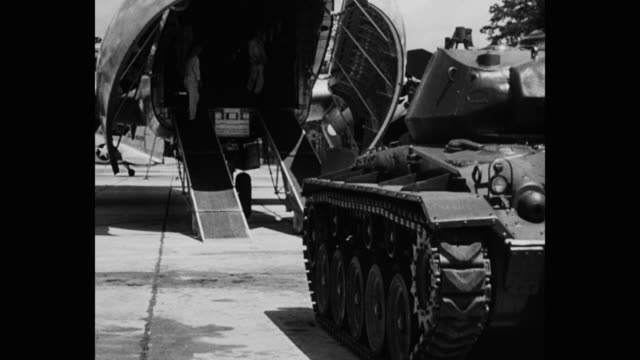 wide shot of armored tank moving towards us military airplane on military base runway - military base stock videos & royalty-free footage