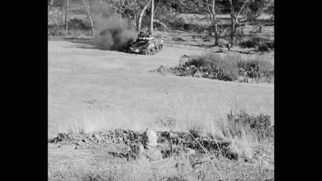 wide shot of army soldier attacking enemies while standing in fighting hole - 戦車点の映像素材/bロール