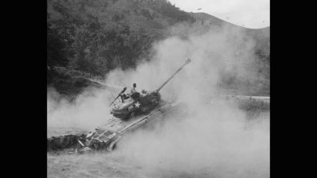 wide shot of army soldier firing with cannon while sitting on armored tank - 戦車点の映像素材/bロール