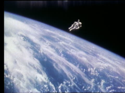 wide shot of astronaut in mobile maneuvering unit above Earth