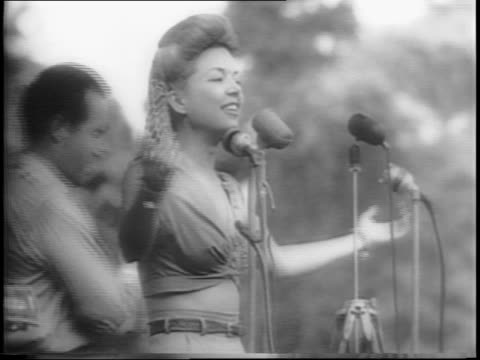 wide shot of audience / medium shot of frances langford singing a song into a microphone beside bob hope while he reacts to her song / close up of... - anno 1944 video stock e b–roll