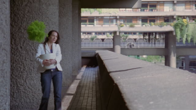 wide shot of balcony of high-rise building / woman carrying potted plant along balcony / london, england - carrying stock videos & royalty-free footage