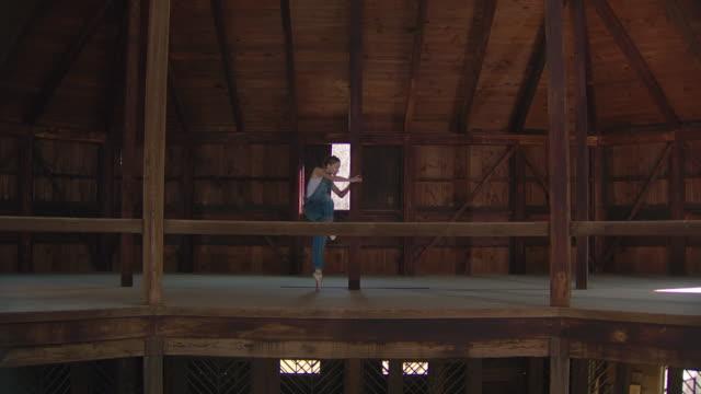 wide shot of ballet dancers on point dancing in wooden barn - アルスター郡点の映像素材/bロール