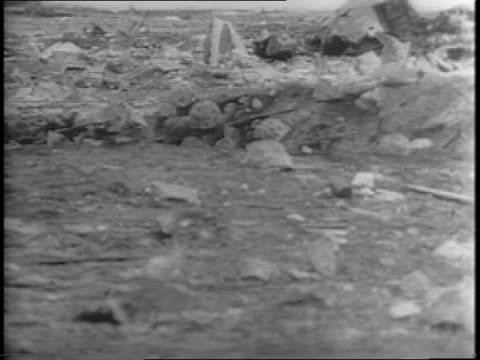 vidéos et rushes de wide shot of beach with soldiers crouching to avoid a sniper in the distance / shots of us soldiers jumping into the trenches and firing their rifles. - évitement