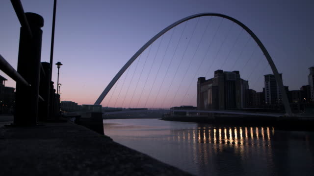 stockvideo's en b-roll-footage met wide shot of birds flying across a beautiful sunrise over newcastle upon tyne's millennium bridge, uk. - newcastle upon tyne