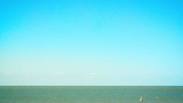 wide shot of blue sky over sea - blue stock videos & royalty-free footage