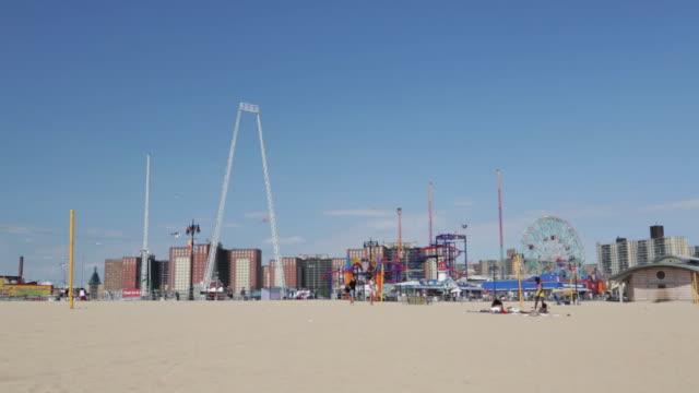 Wide shot of boardwalk amusement park and apartment buildings