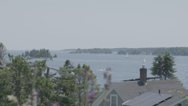 Wide shot of boats behind rooftops in Boothbay Harbor