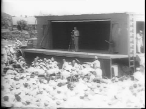 wide shot of bob hope on stage with audience in foreground / medium shots of soldiers laughing - anno 1944 video stock e b–roll