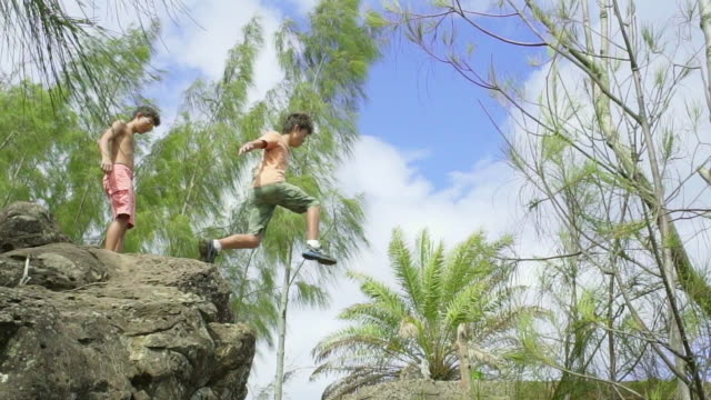 wide shot of boy jumping a rock crevace in slow motion - felsblock stock-videos und b-roll-filmmaterial