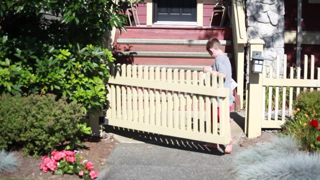 vídeos y material grabado en eventos de stock de wide shot of boy opening picket fence gate, runs up stairs and drops paper in front of front door, then runs down the stairs meeting a young girl on a sunny spring day - kelly mason videos