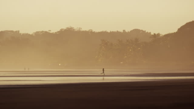 """wide shot of boy running on beach / esterillos, punta arenas, "" - only boys stock videos and b-roll footage"