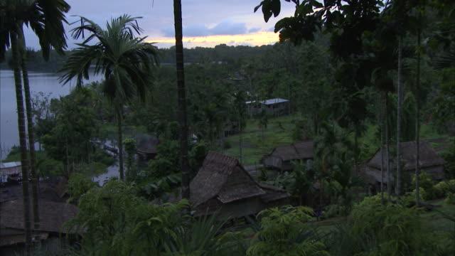 vidéos et rushes de wide shot of boy walking through tribal village at sunset - cabane structure bâtie