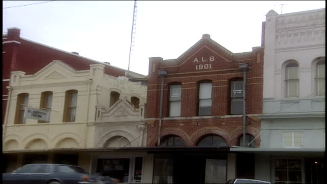wide shot of buildings of main st in small town in bryan, texas - targa con nome della via video stock e b–roll