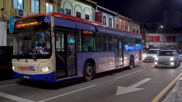 wide shot of bus on the busy street , kuala lumpur, malaysia - sydostasien bildbanksvideor och videomaterial från bakom kulisserna