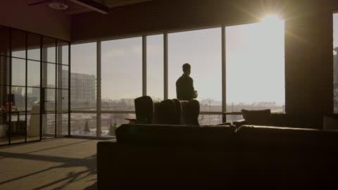 stockvideo's en b-roll-footage met wide shot of businessman drinking coffee in office / lehi, utah, united states - window