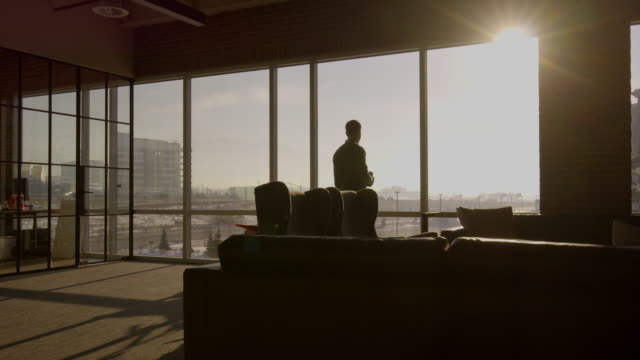 wide shot of businessman drinking coffee in office / lehi, utah, united states - 景色を眺める点の映像素材/bロール