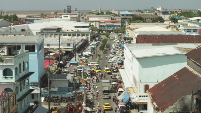 wide shot of busy street with market and crowds - guyana stock videos & royalty-free footage