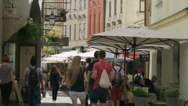 vidéos et rushes de wide shot of busy street with restaurants and shops / ljubljana, slovenia - ljubljana