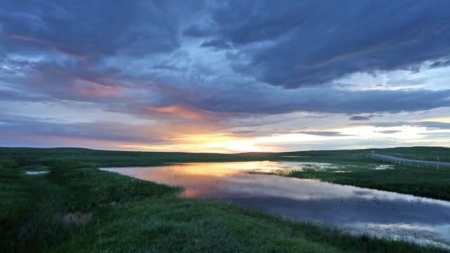 wide shot of calm lake on prairie with dramatic clouds at sunrise. - prärie stock-videos und b-roll-filmmaterial