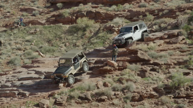 Wide shot of cars descending rocks in desert / Moab, Utah, United States