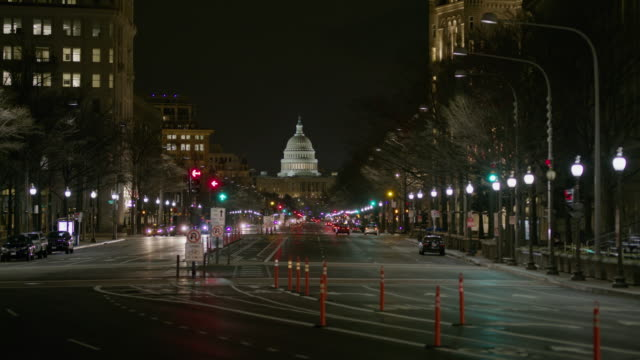 vídeos de stock, filmes e b-roll de wide shot of cars driving in city at night / washington, district of columbia, united states - washington dc