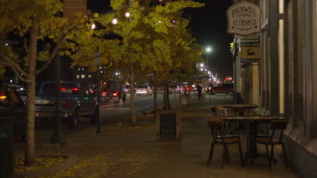 wide shot of cars driving in city near sidewalk / provo, utah, united states - provo stock-videos und b-roll-filmmaterial