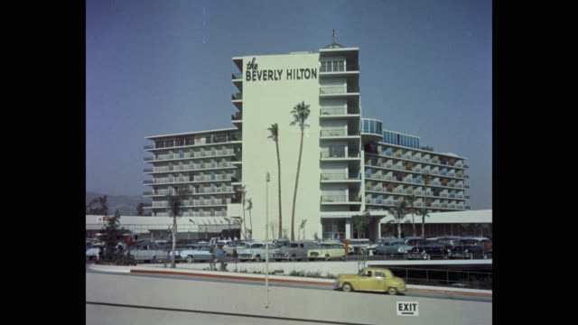 wide shot of cars driving on street in front of the beverly hilton hotel, beverly hills, california, usa - the beverly hilton hotel stock videos & royalty-free footage
