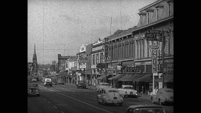 stockvideo's en b-roll-footage met wide shot of cars driving on street in old town, usa - straatnaambord