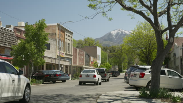 Wide shot of cars driving on street in small town / Payson, Utah, United States