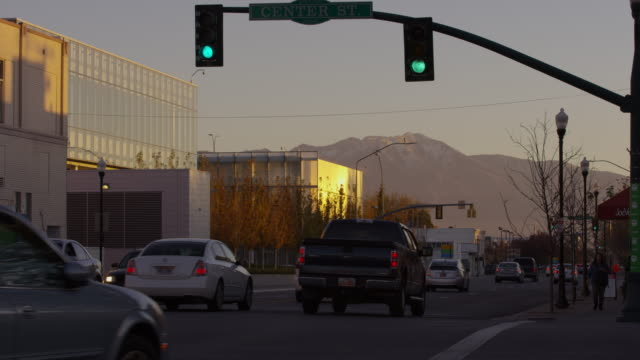 vídeos de stock e filmes b-roll de wide shot of cars driving under traffic light / provo, utah, united states - provo