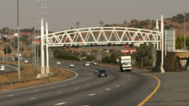 Wide shot of cars on highway passing through toll gantry/ Johannesburg/ South Africa