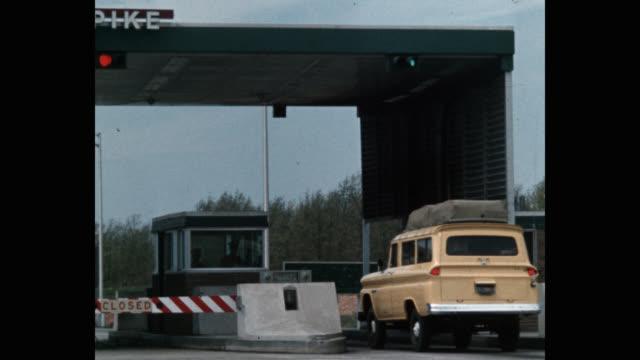 vídeos de stock e filmes b-roll de wide shot of cars passing through toll booth - cabina de portagem